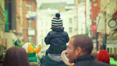 Crowd of people walking and with child with ADHD on shoulder of man