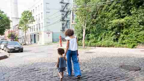 Mother helping daughter cope with ADHD by taking walk down cobblestone street