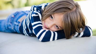 A happy child with ADHD lays on her stomach and smiles