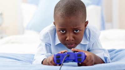 Young boy with ADHD intently playing video games and neglects chores