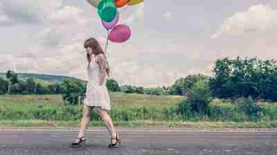 Woman with ADHD walking down road with balloons in hand on birthday
