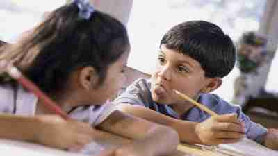 Boy with ADHD sticking tongue out at girl next to him in classroom