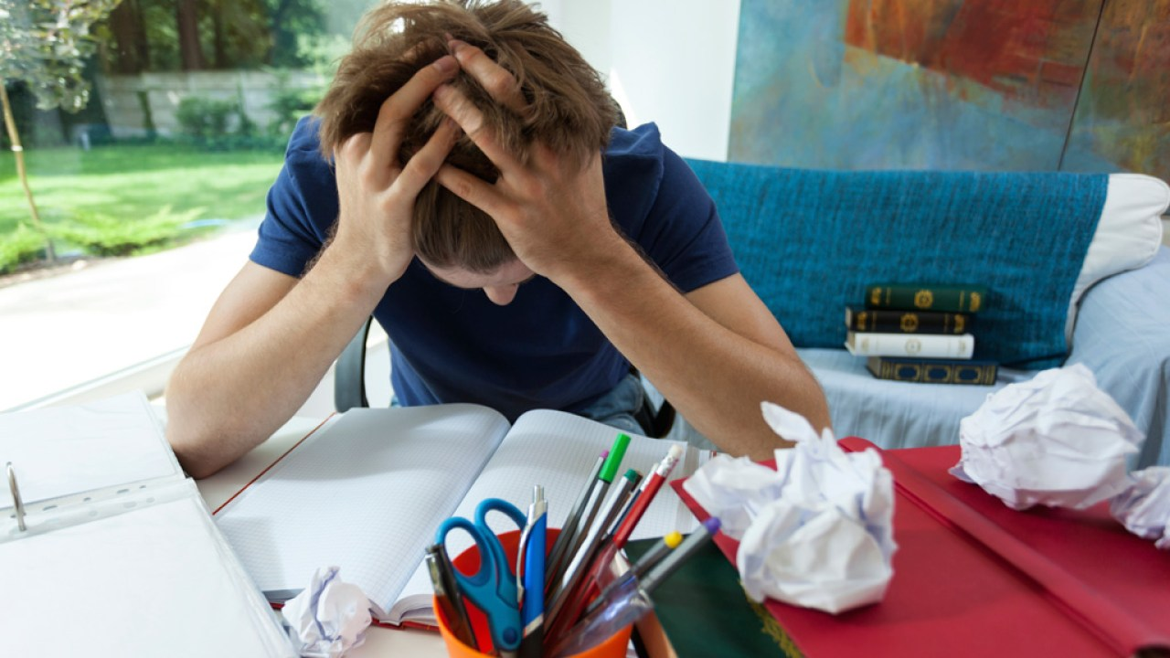 ADHD student with head in hands surrounded by books and paper overwhelmed by disorganization in room