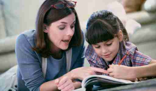 A mother who learned how to homeschool her daughter with ADHD, pictured laying next to her, both reading