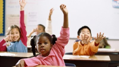 Children raising their hands in a classroom, following the rules for answering a question