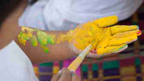 A boy with ADHD paints his hand yellow to bolster his kinesthetic learning style.