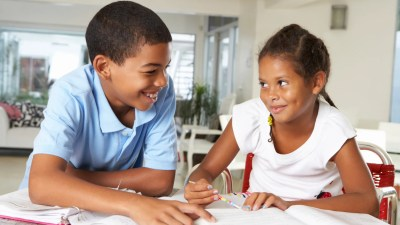 Two siblings with ADHD, working together to get their homework done faster.