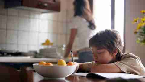 Boy with ADHD doing homework in kitchen while mom cooks