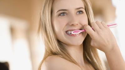 A teenager with ADHD brushes her teeth as part of a morning routine