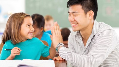 Introducing your child with ADHD to his teacher before the school year starts will help improve their relationship, like this teacher and student high-fiving