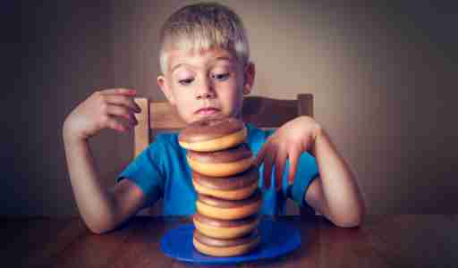 A boy with ADHD, staring at a tall pile of donuts with sugar