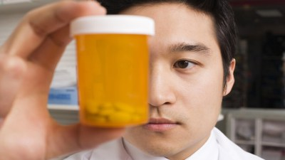 Adderall dosage: Doctor holding pill bottle up to face with ADHD medication inside it