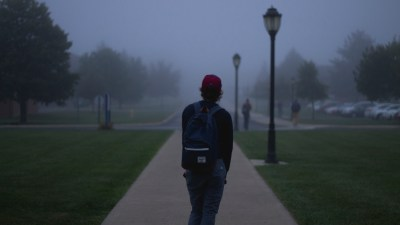 College student with ADHD looking out at campus at nightfall alone