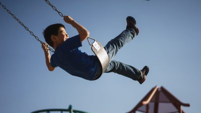 A boy with ADHD is on the swings after a behavior therapy session.