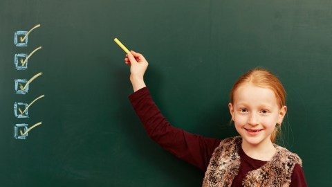 A girl writing on a chalkboard, checking off ways to help herself focus in school