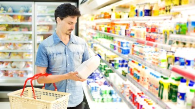 """A man with ADHD puts milk in his basket at the supermarket, while thinking, """"I hate grocery shopping."""""""