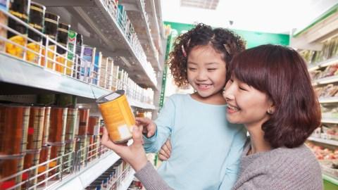 A mom with ADHD and her daughter hold an item on their list at the supermarket. With a list, she doesn't hate grocery shopping anymore.