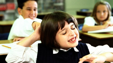 portrait of a school boy (8-10) pulling a girls hair in class