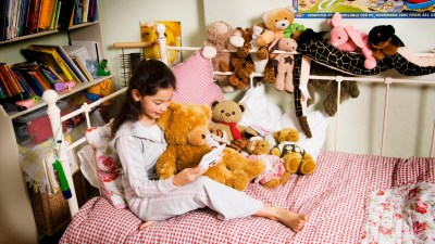 A young girl using stuffed animals to help her focus on homework