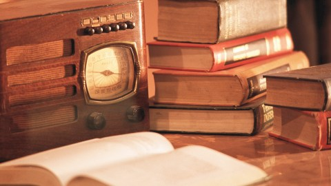 A desk shows an old radio and books, ways to get creative to help with focus.