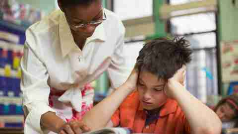 A teacher helping a child with math problems in the classroom, in accordance with his IEP