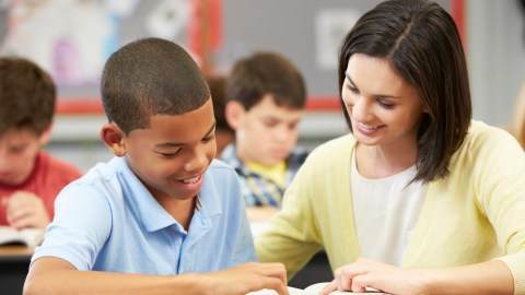 A teacher working on reading problems with a student, in accordance with his IEP