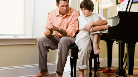 Serious father having discussion with his son about the problems he's having with his IEP