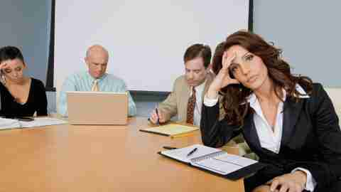 A woman being ignored during her child's IEP meeting, unable to bring up her problems with it