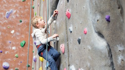 A ADHD boy enjoying rock climbing at indoor climbing gym, healthy and active lifestyle concept