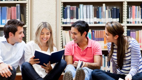 Group of students sitting in the library reading advice books for teens