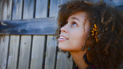 A teen girl with a flower in her hair thinking about some advice she received recently
