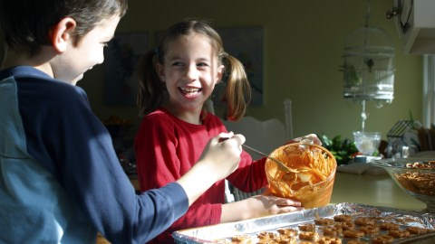 Two children making cookies thanks to positive parenting