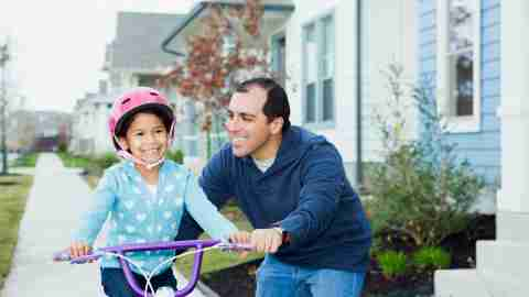 Father using positive parenting techniques to help his daughter learn how to ride a bicycle