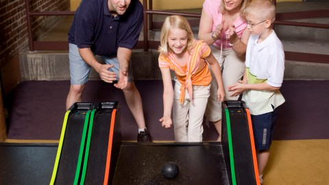 A happy family spending time together and playing games in an arcade, thanks to positive parenting