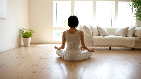 Young woman performing yoga pose in living room to dull her hypersensitivity.