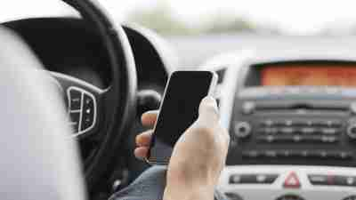 A driver uses their cell phone as an ADHD organizational tool while driving