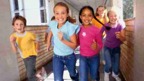 A group of young children are running with endless energy, another positive trait of ADHD.