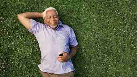 A senior man with ADHD lies in the grass and listens to music.