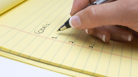 A woman with ADHD writes a list of goals on her to-do list.