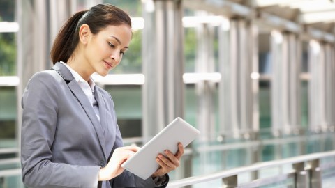 A businesswoman uses a tablet to stop wasting time and get more done.