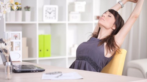 A woman with ADHD taking a break to stretch in her office.