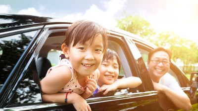 happy little girl with ADHD riding with her family sitting in the car