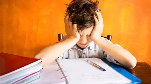 A young boy sitting in a classroom and struggling to manage his behavior