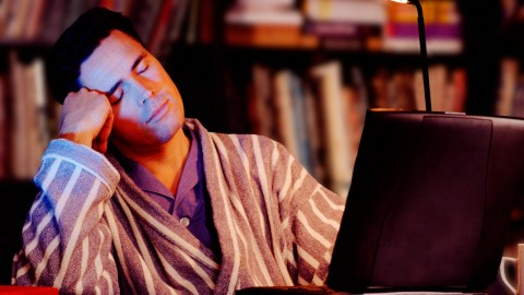 A man who suffers from sleeplessness due to anxiety falls asleep at his computer
