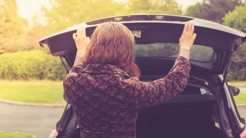A woman with ADHD opens the trunk of her car and tries to remember the task she went outside for.