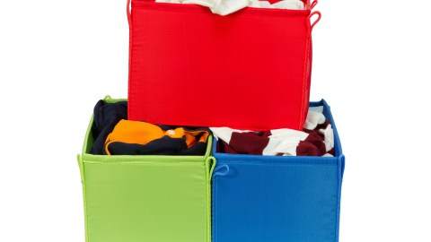 Three organized canvas bozes full of clothes. A system for laundry can reduce ADHD stress.
