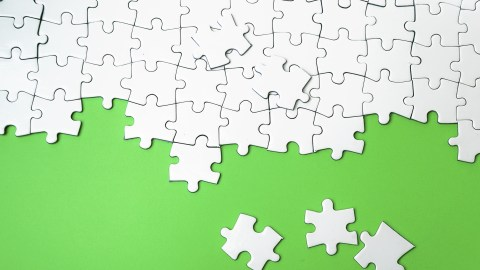 White puzzle pieces on a green background, a metaphor for leaving projects incomplete when ADHD stress is too great