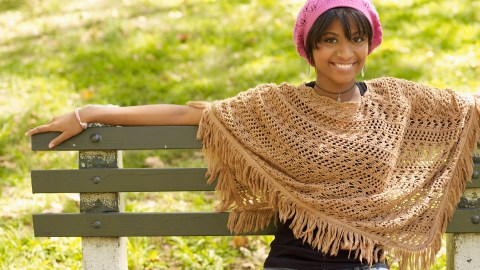 A woman with ADHD wears a knit hat and poncho and sits on a park bench