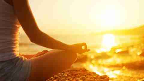 A woman with ADHD sits in lotus position on rocks overlooking the beach at sunset