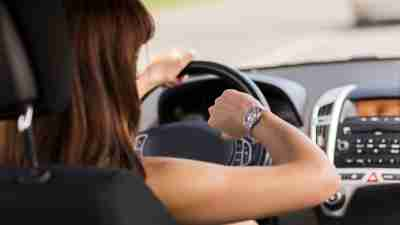 A woman with ADHD driving a car looks at her watch. She is running late after wasting time earlier.